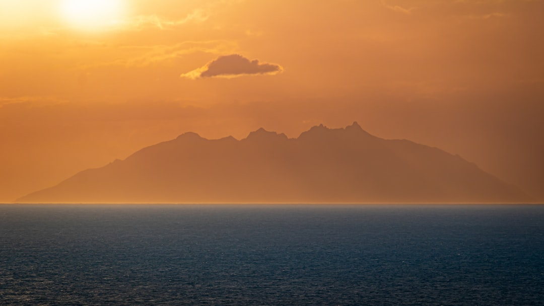 distant islet during sunset surrounded by the sea