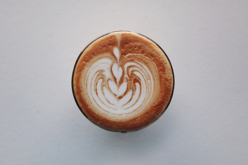 brown and white ceramic cup with heart shaped coffee