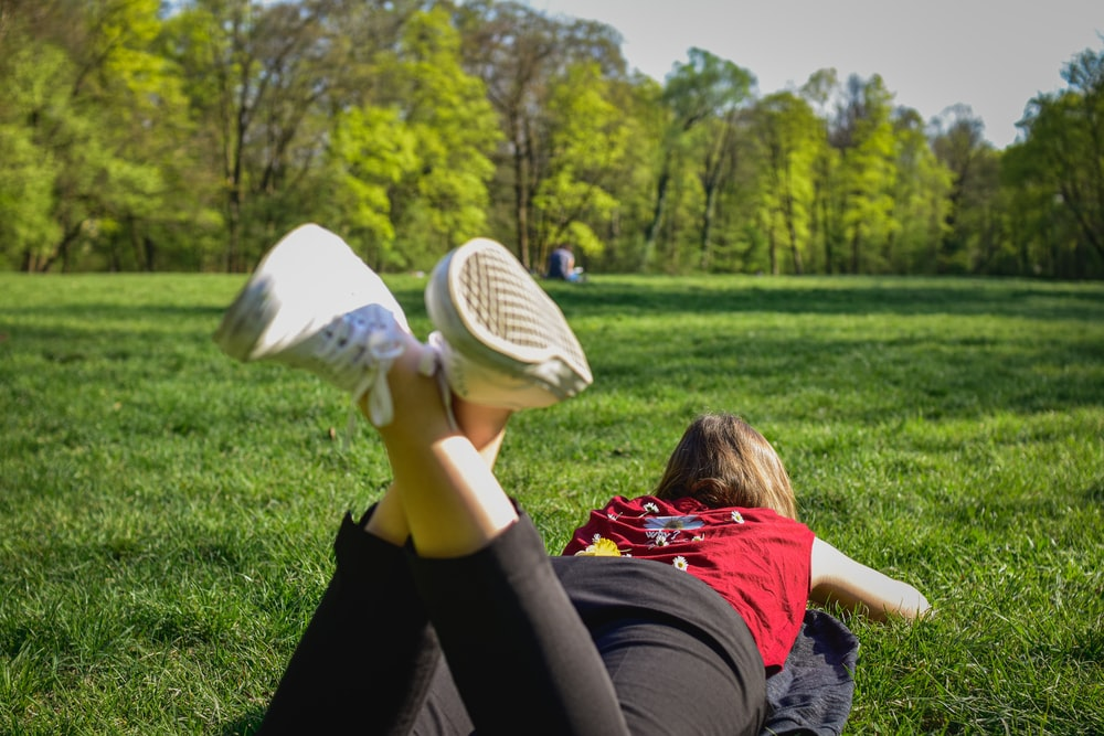 woman in black pants and red shirt lying on green grass field during daytime