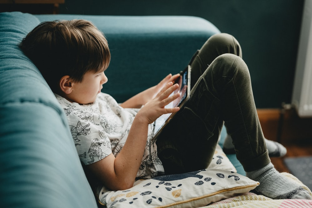 boy in white shirt and black pants sitting on couch