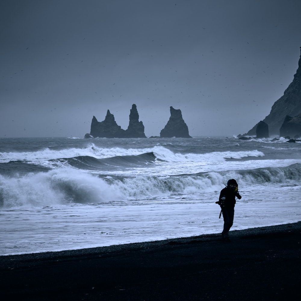 silhouette of person standing on seashore near ocean waves during daytime