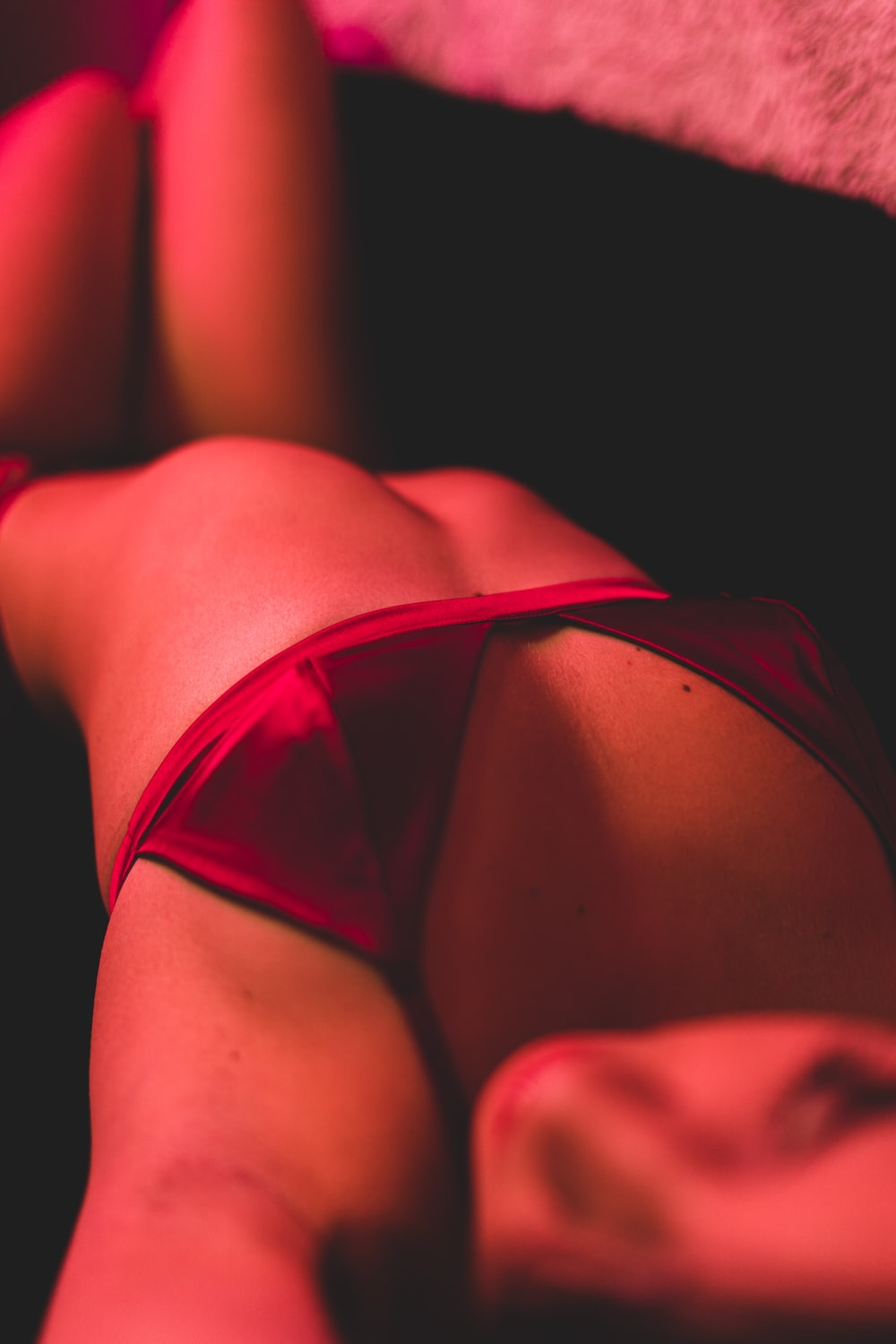 woman in red panty lying on black textile