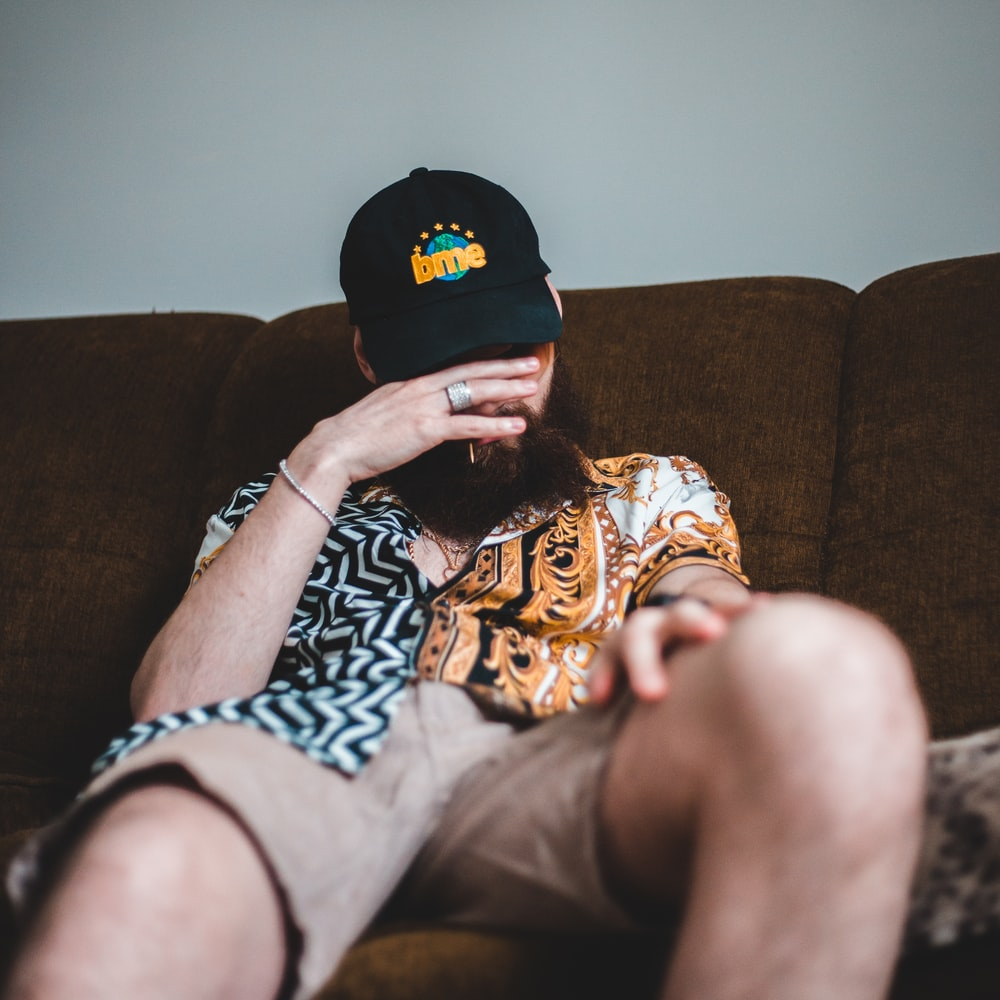 person in black and orange cap and black and white shirt lying on brown sofa