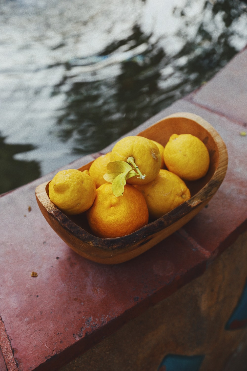 yellow citrus fruits on brown wooden bowl
