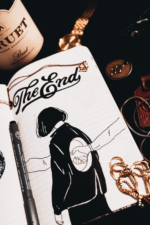 white and black pen beside white notebook