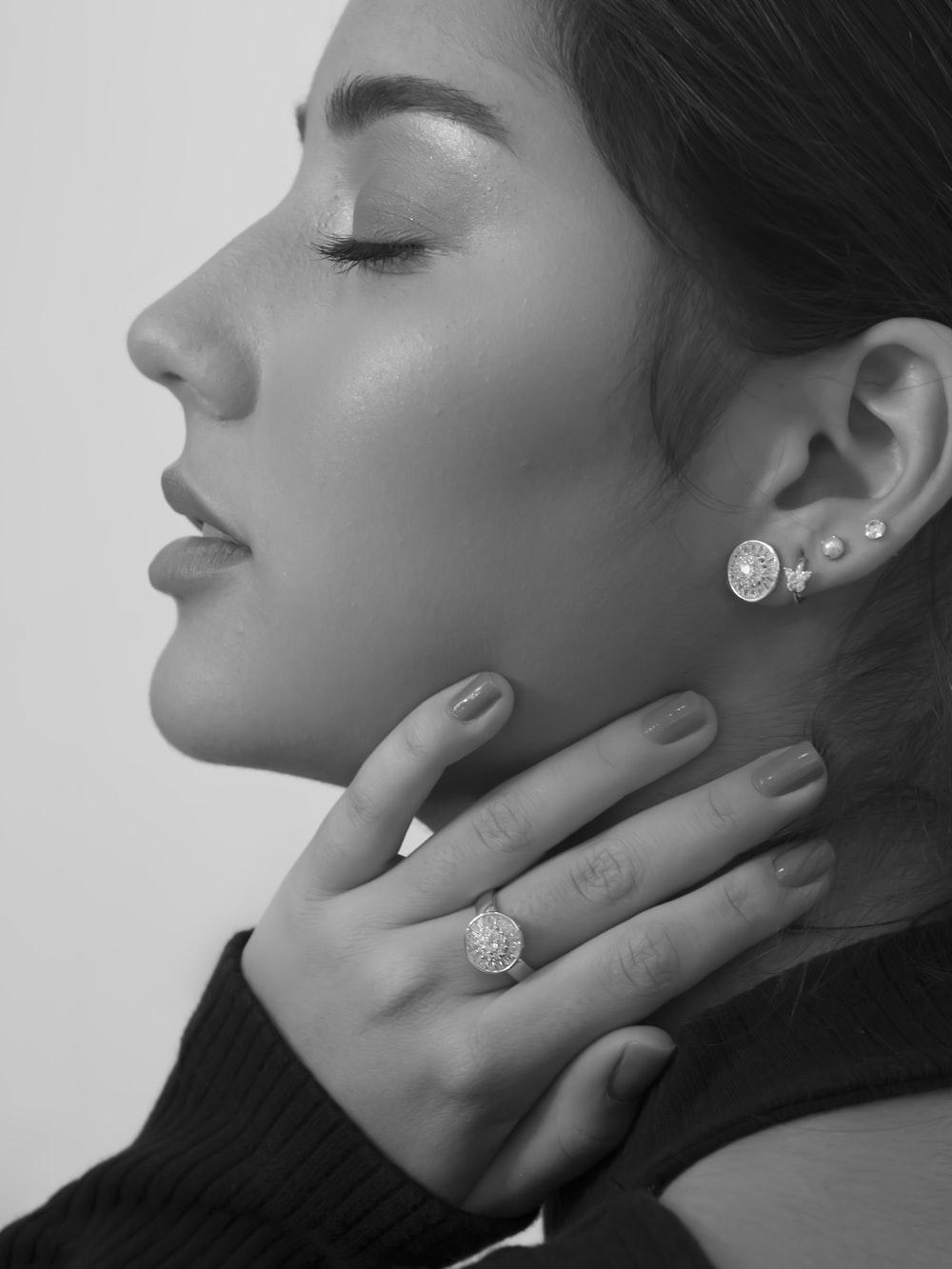 grayscale photo of woman wearing silver diamond stud earrings