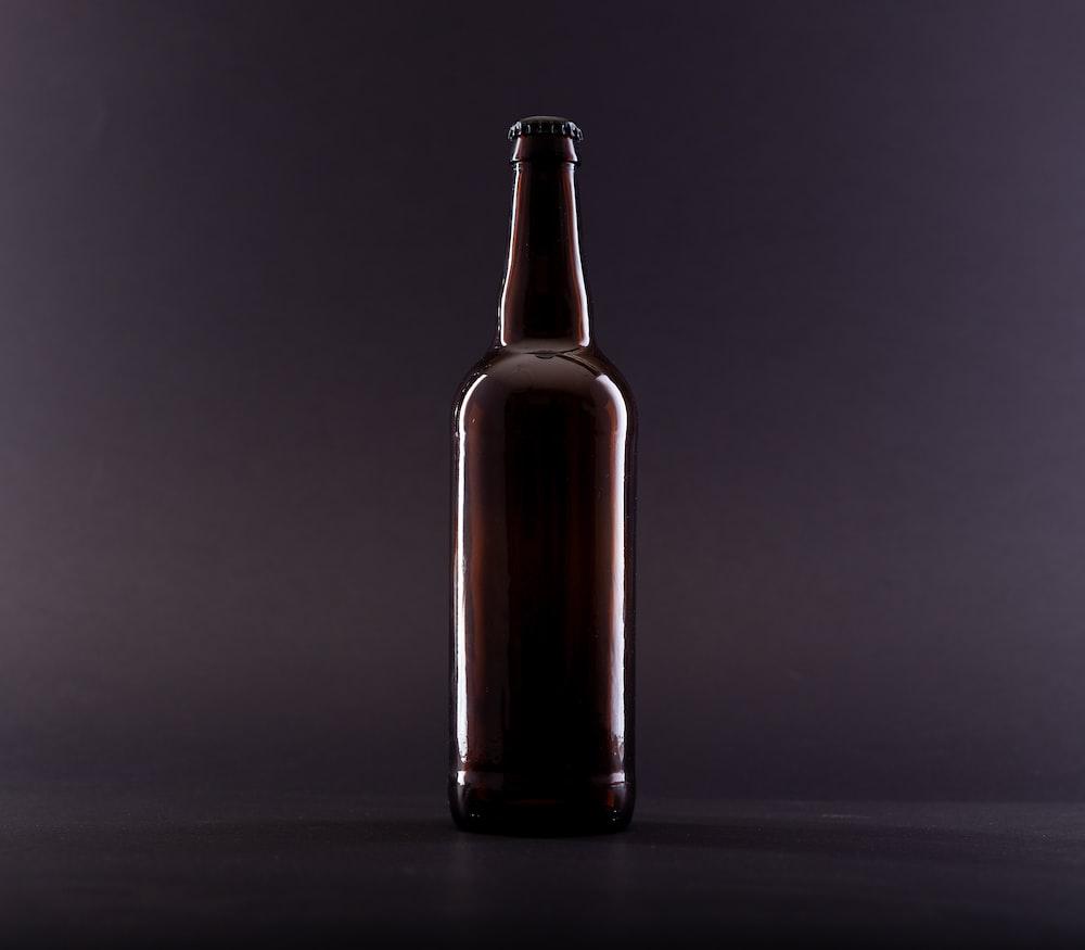 brown glass bottle on black surface