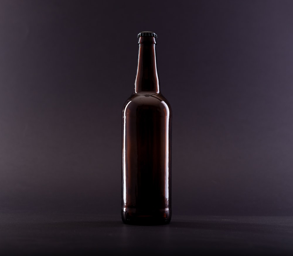 brown glass bottle on black surface