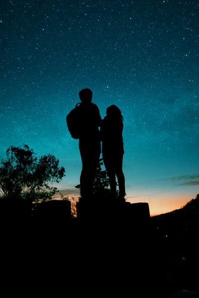 silhouette of man and woman kissing under blue sky during night time