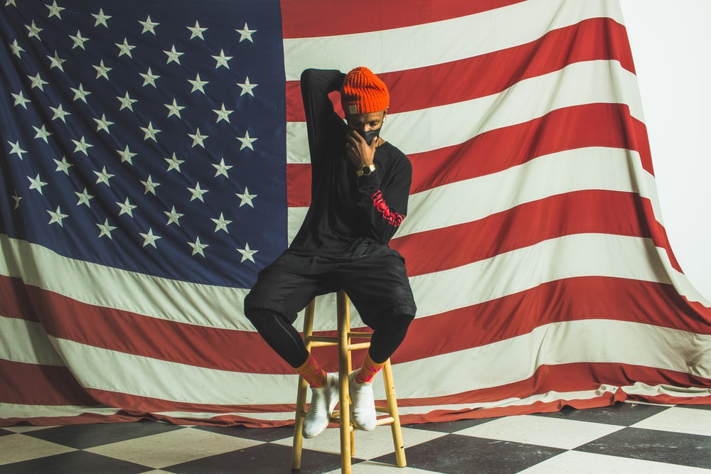 man in black leather jacket and pants sitting on chair near flag of america