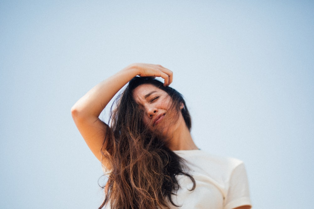woman in white shirt covering her face with her hair