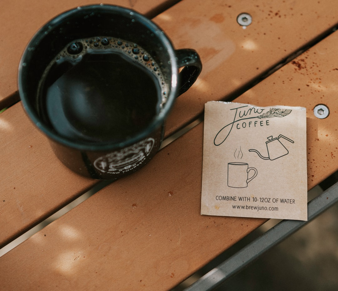Black Ceramic Mug On Brown Wooden Table - unsplash