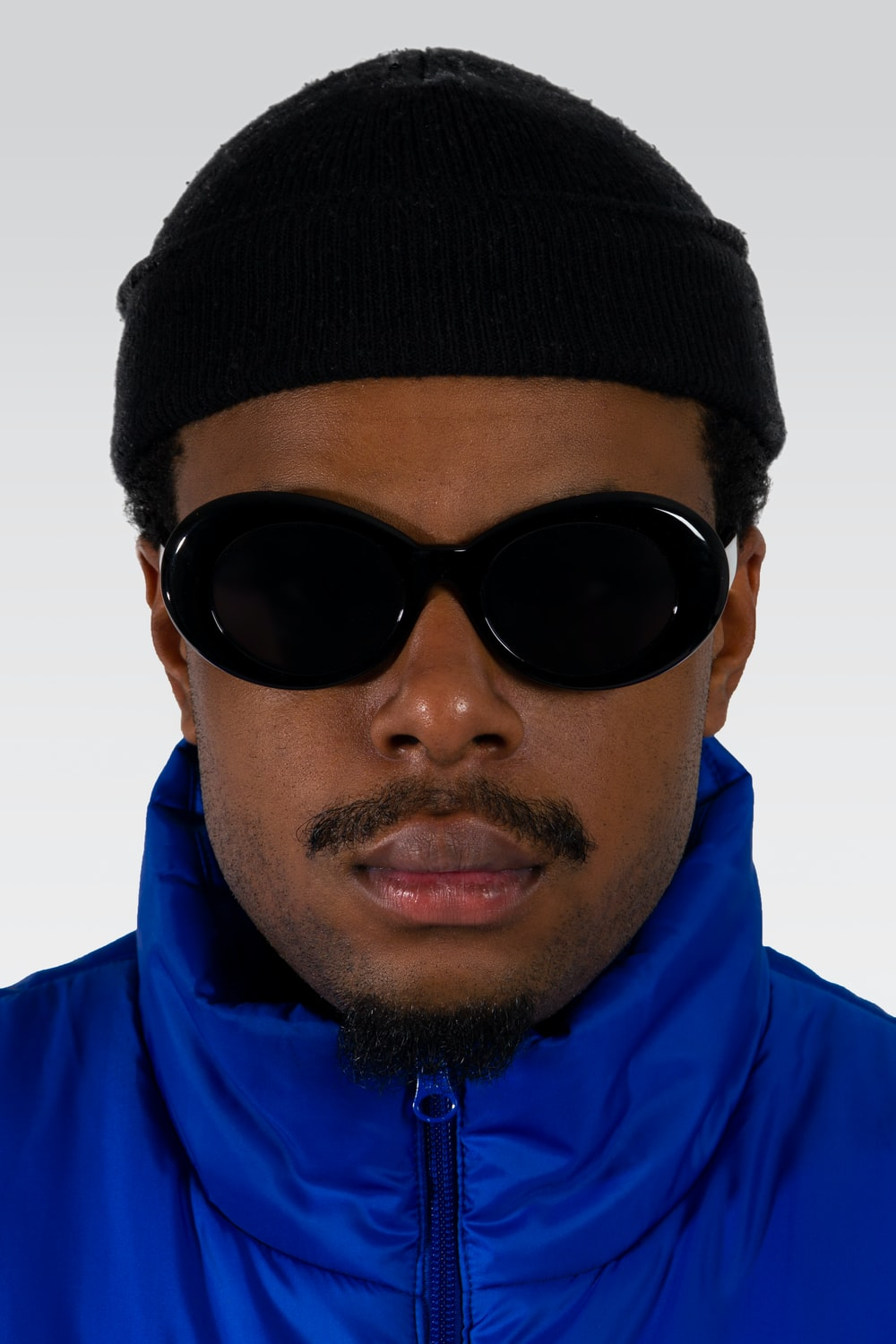 man in blue jacket wearing black knit cap and black sunglasses