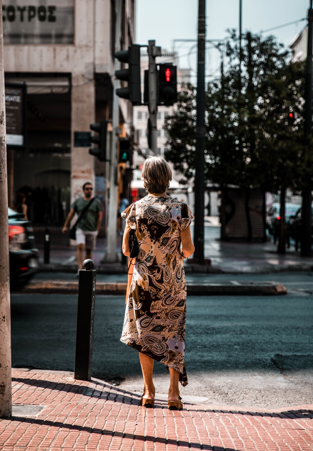 woman in yellow and black floral dress standing on sidewalk during daytime