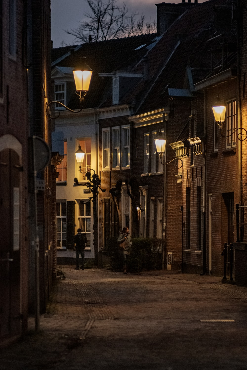 empty street with light posts between buildings during night time