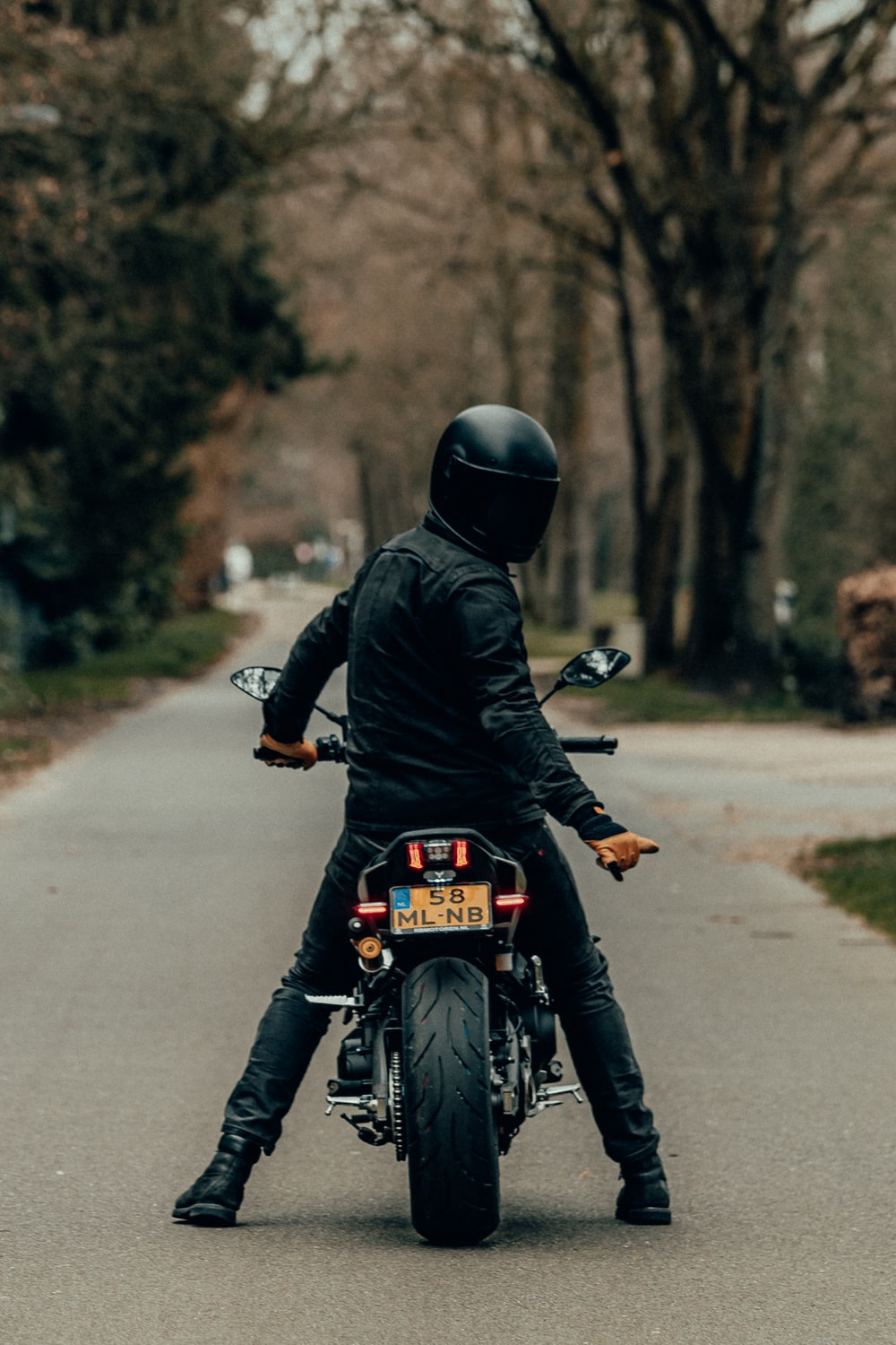 man in black leather jacket riding motorcycle on road during daytime