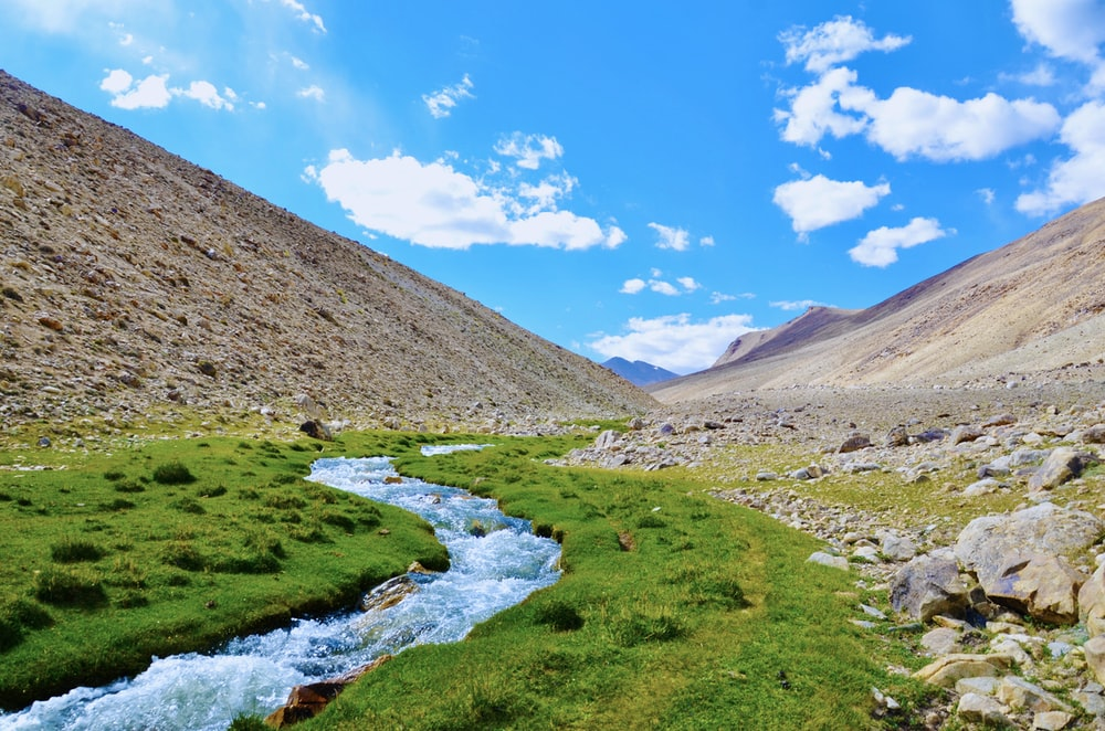 river in between brown mountains under blue sky during daytime