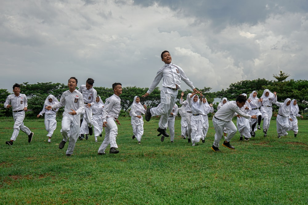 group of people in white uniform on green grass field during daytime