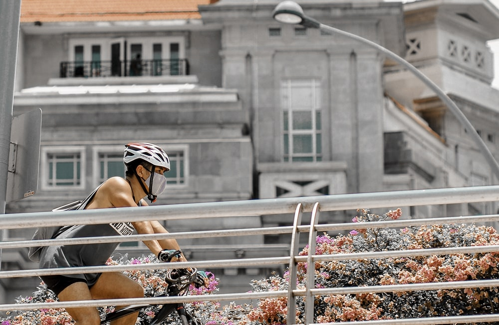 woman in white and black helmet sitting on white metal railings during daytime