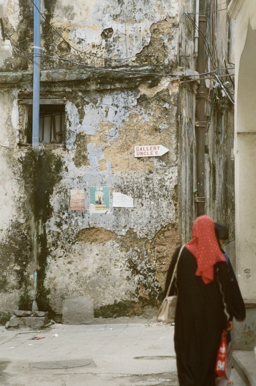 woman in red hijab standing in front of white wooden door
