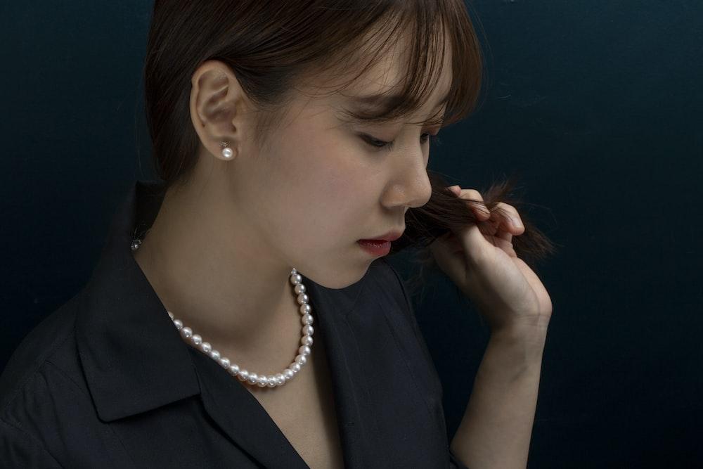 woman in black blazer wearing white pearl necklace