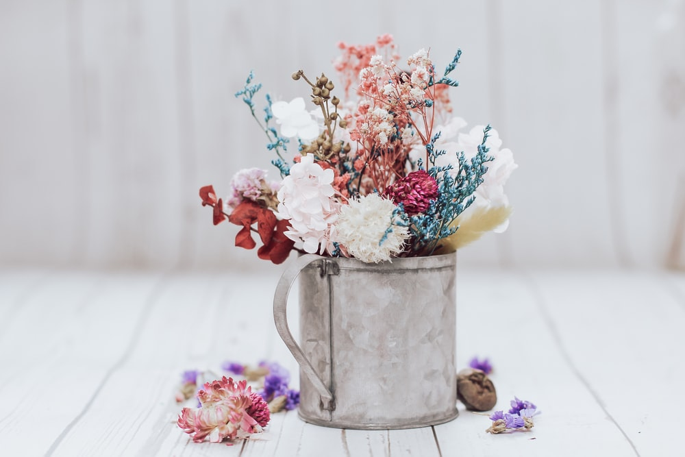 white pink and yellow flowers in gray steel watering can