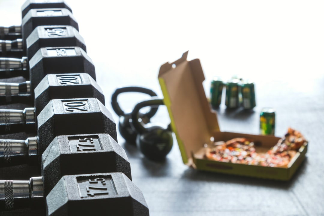 dumbbell weights in focus with beer and pizza off to one side soft focus