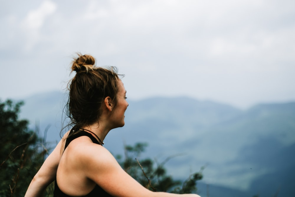 woman in black tank top looking at the mountains during daytime