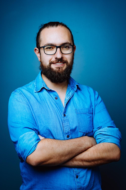 man in blue button up shirt wearing black framed eyeglasses