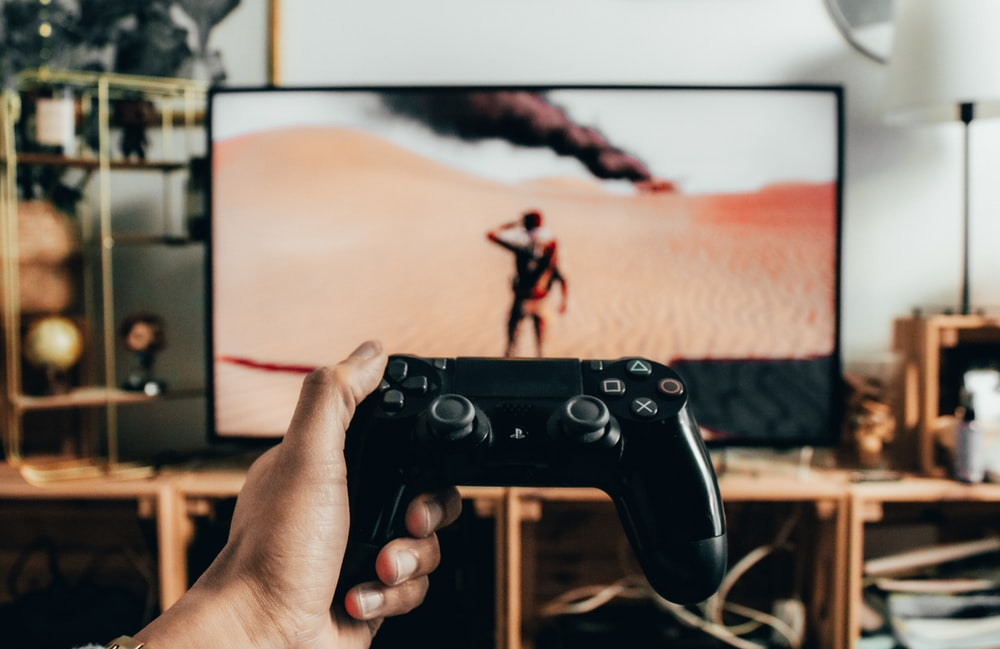 person holding black sony ps 4 controller