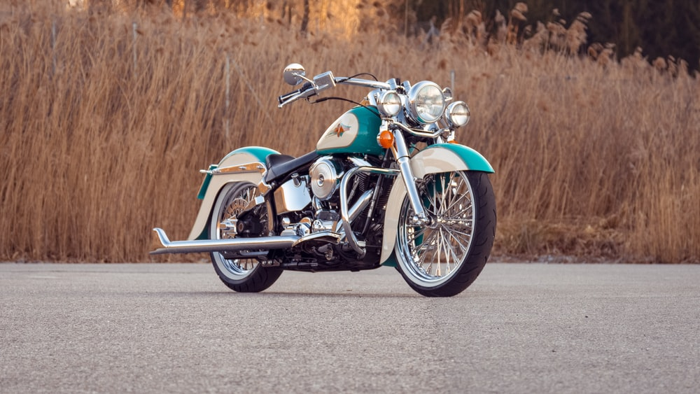 blue and silver cruiser motorcycle on gray asphalt road during daytime