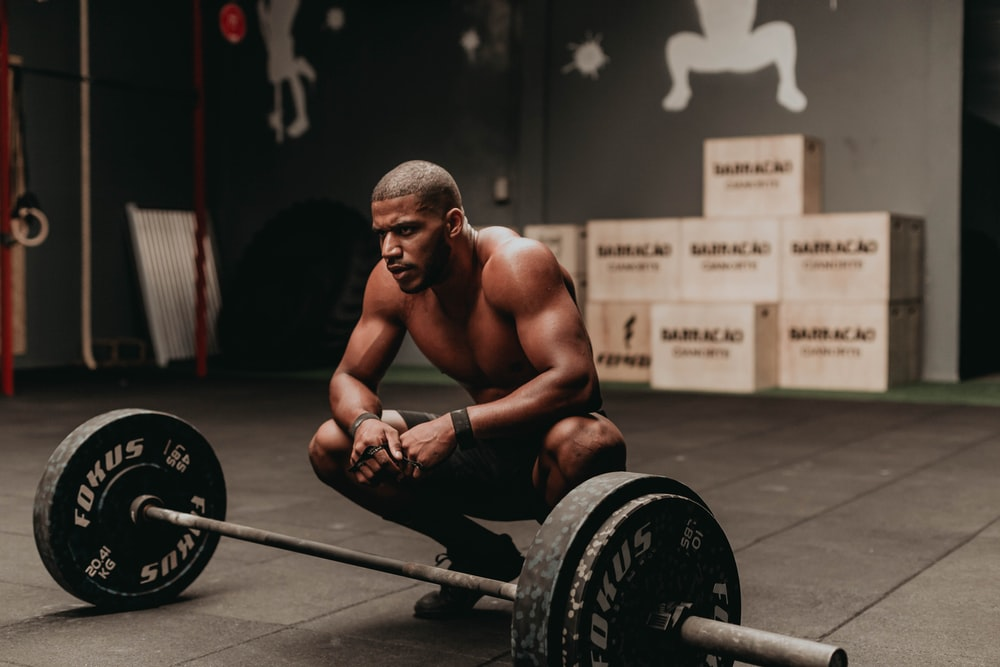 topless man sitting on black and gray barbell