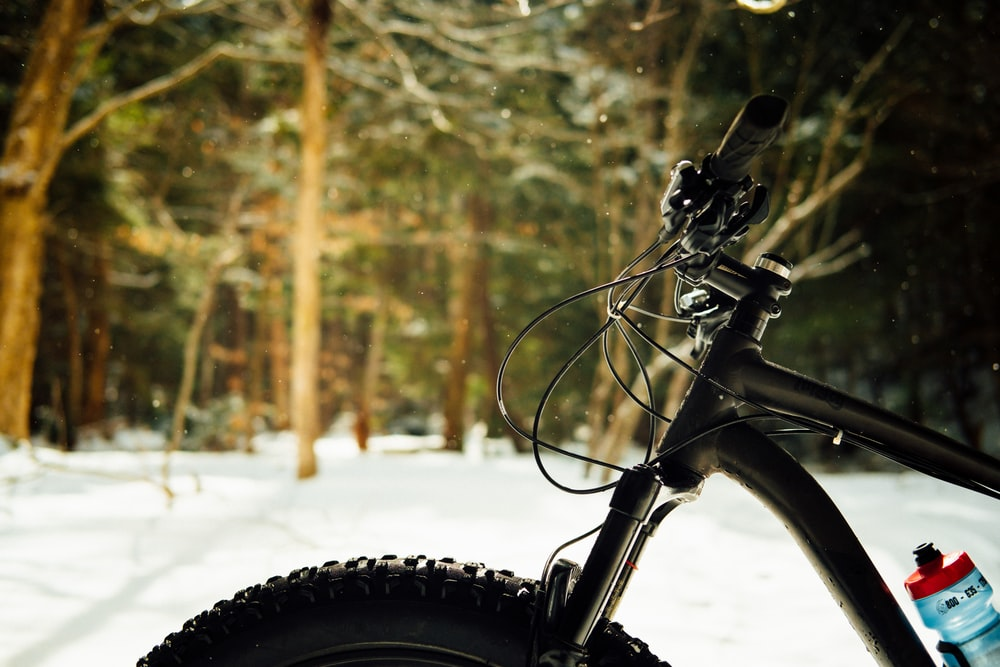 black bicycle on snow covered ground during daytime