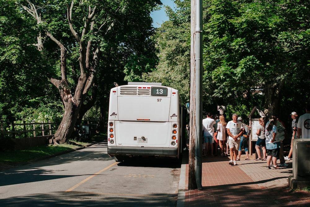 people walking on sidewalk near white van during daytime