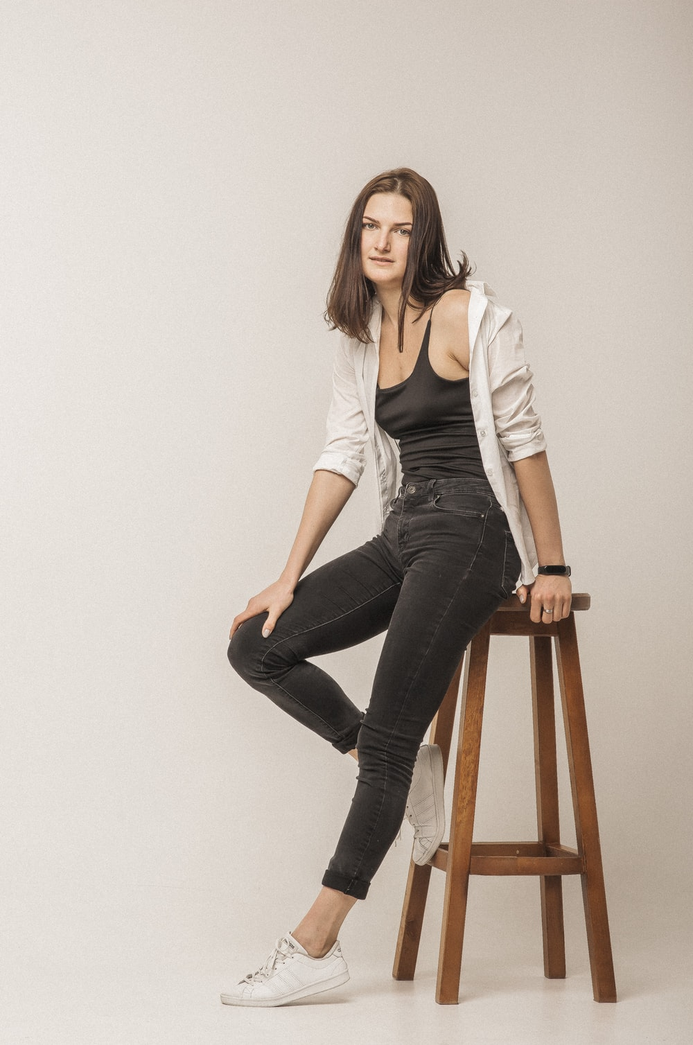 woman in white long sleeve shirt and black denim jeans sitting on brown wooden chair