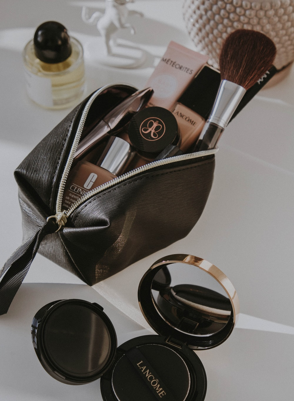 black leather bag with makeup brushes and makeup brushes
