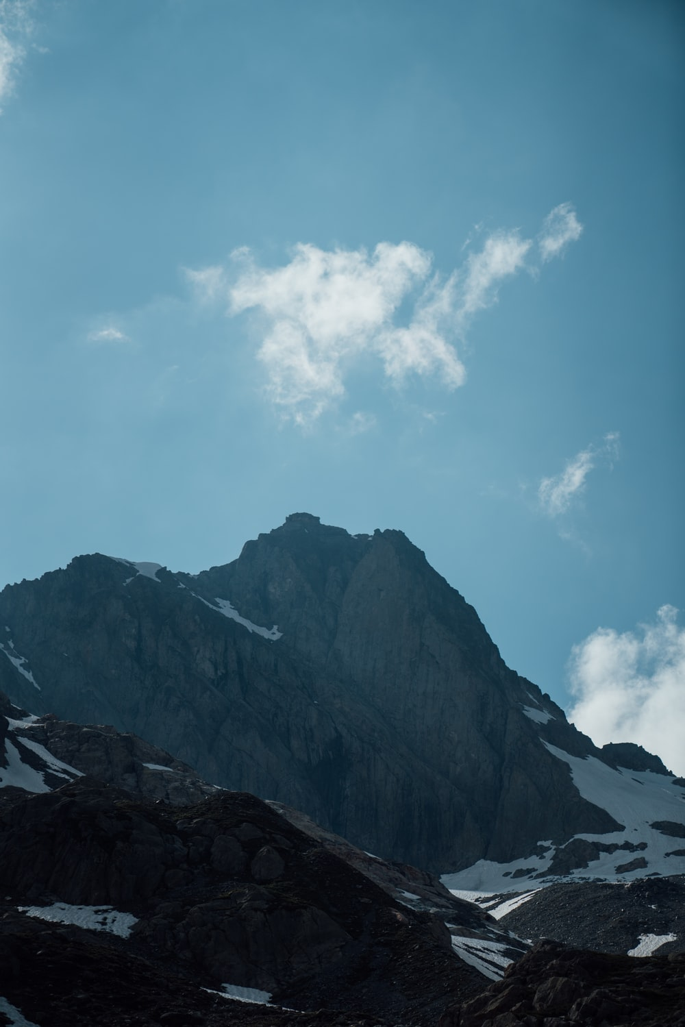 rocky mountain under white clouds and blue sky during daytime