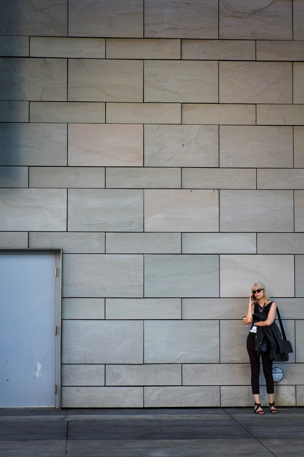 woman in black long sleeve shirt and black pants standing beside blue wall