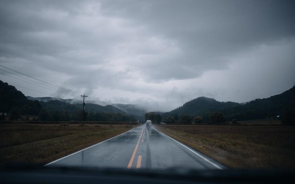 gray asphalt road between green grass field under gray cloudy sky during daytime