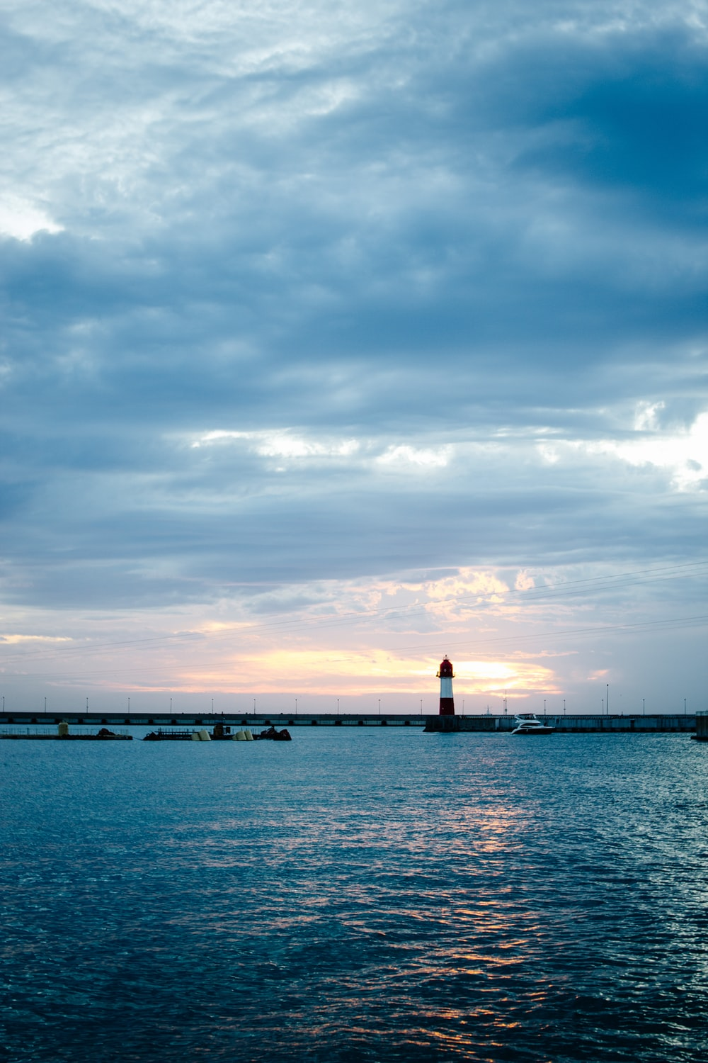 silhouette of lighthouse on sea dock under cloudy sky during daytime