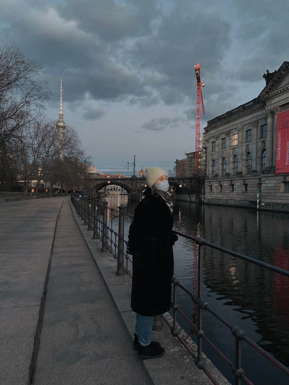 woman in black coat standing on sidewalk near body of water during daytime