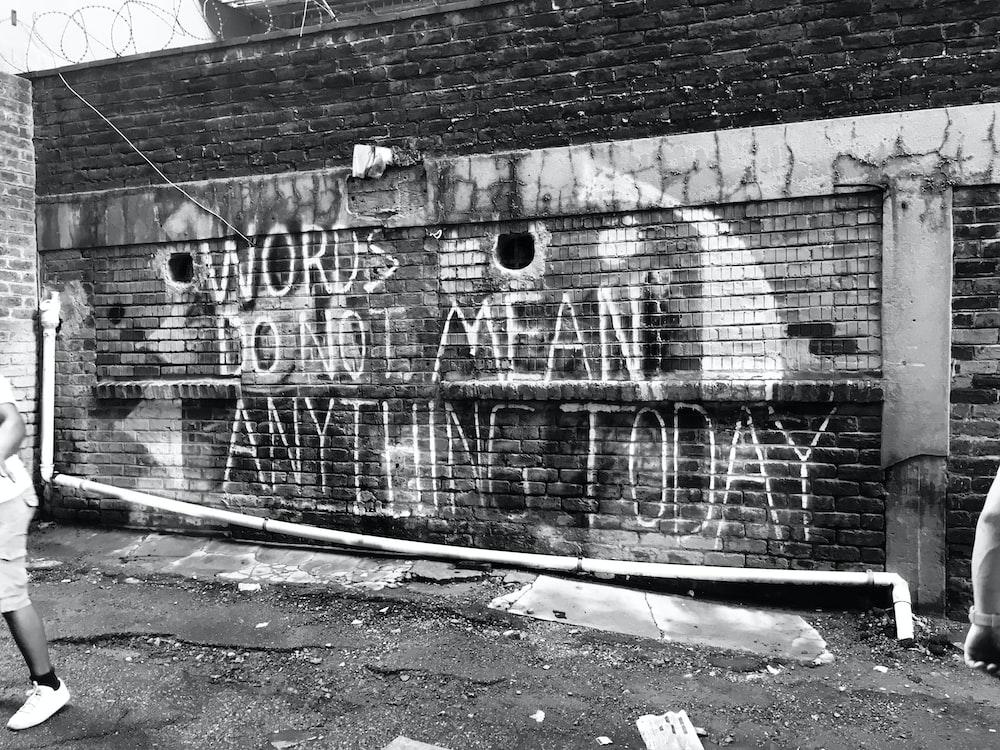 grayscale photo of graffiti on wall