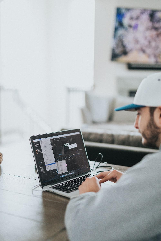 man in white shirt using black laptop computer