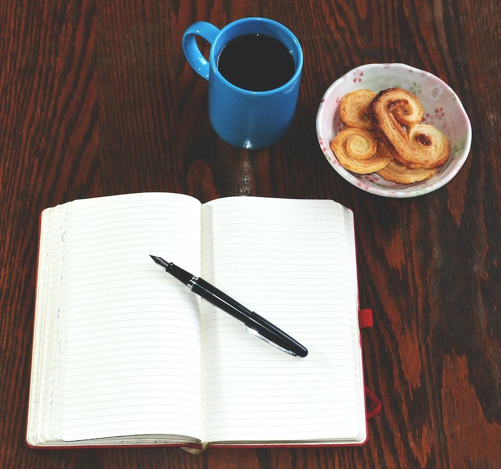 red ceramic mug beside black click pen on white paper