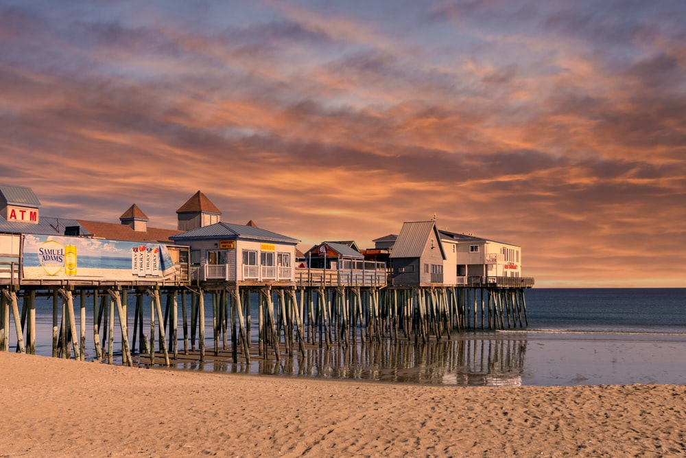 white and brown wooden house on sea shore during sunset