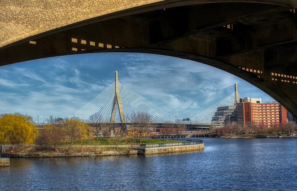 brown bridge over river under blue sky during daytime
