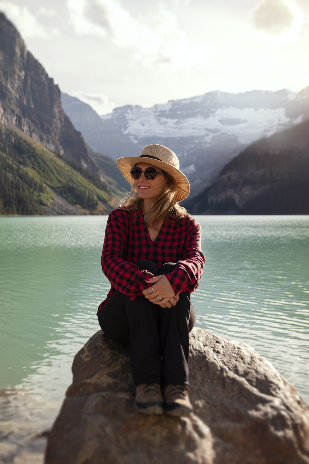 woman in red and white plaid dress shirt and black pants sitting on rock near body
