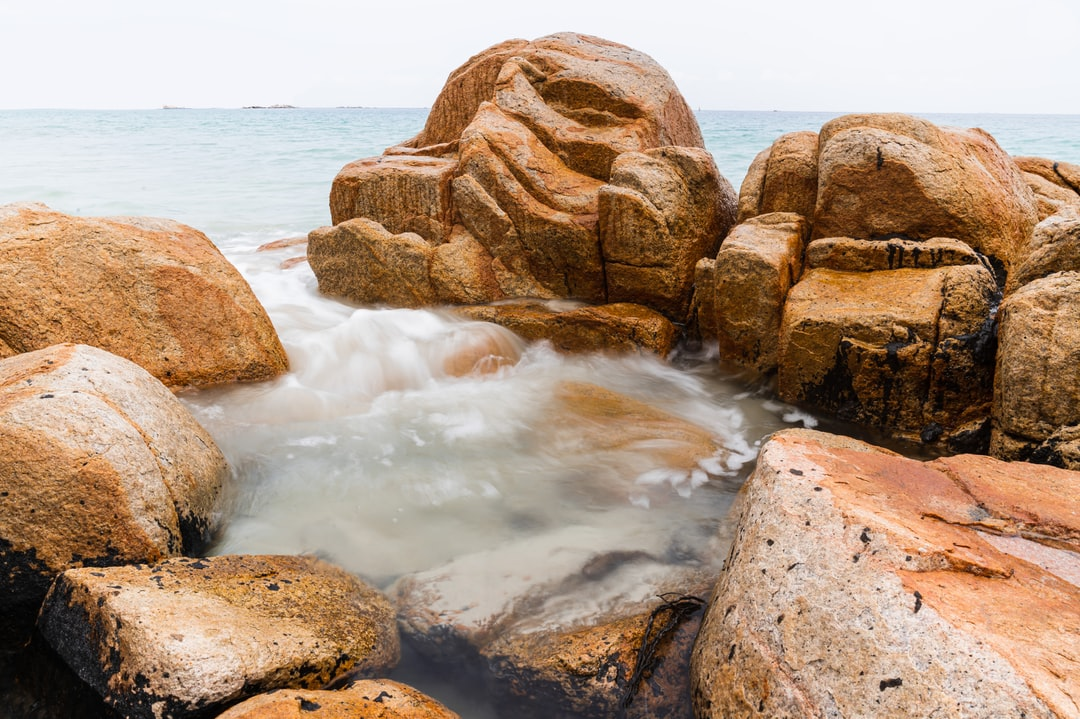 Wave into this tiny gulf of rocks is captured by low shutter speed setting to give a smooth, light, cotton-like texture.