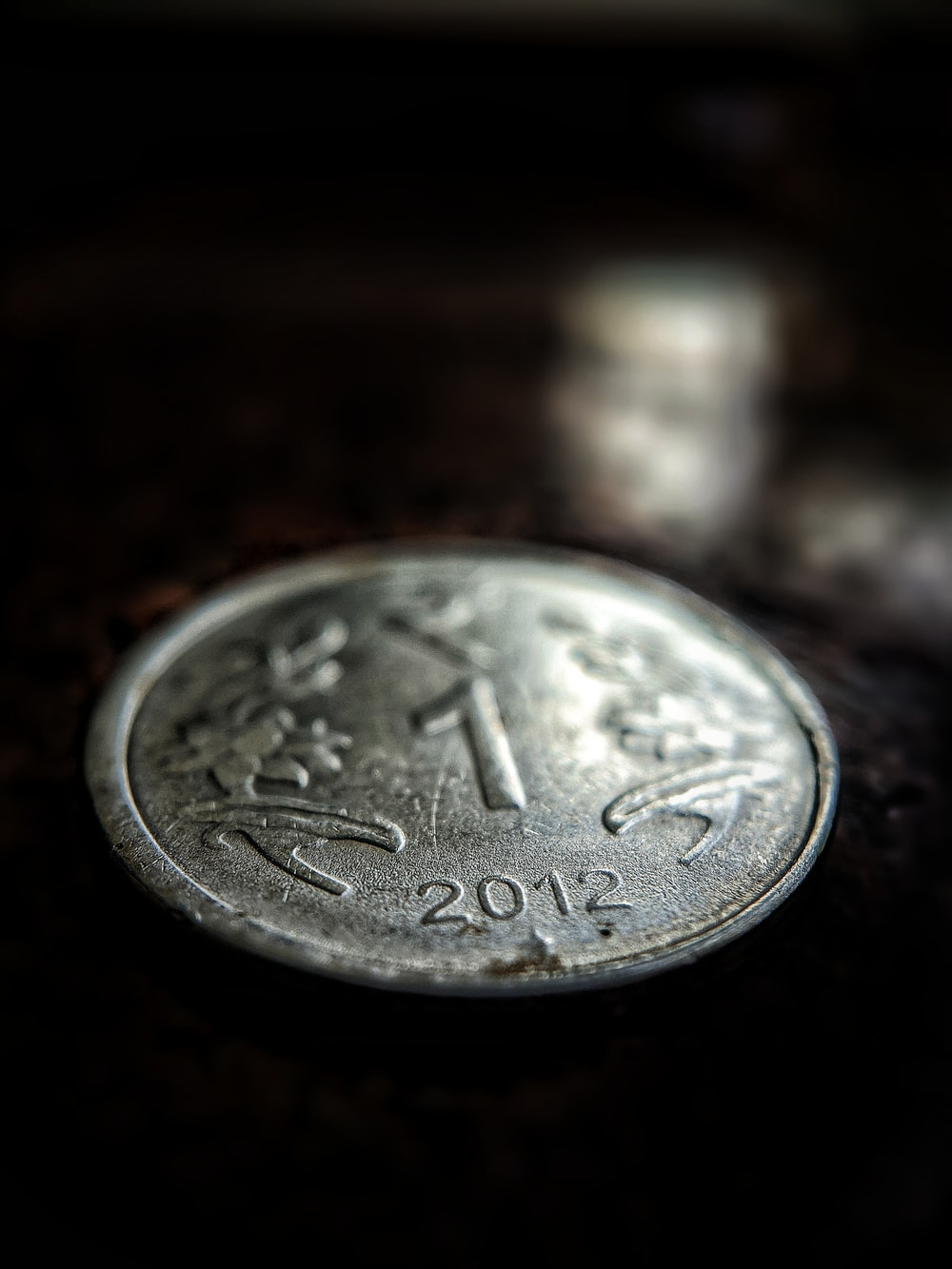 silver round coin on brown surface