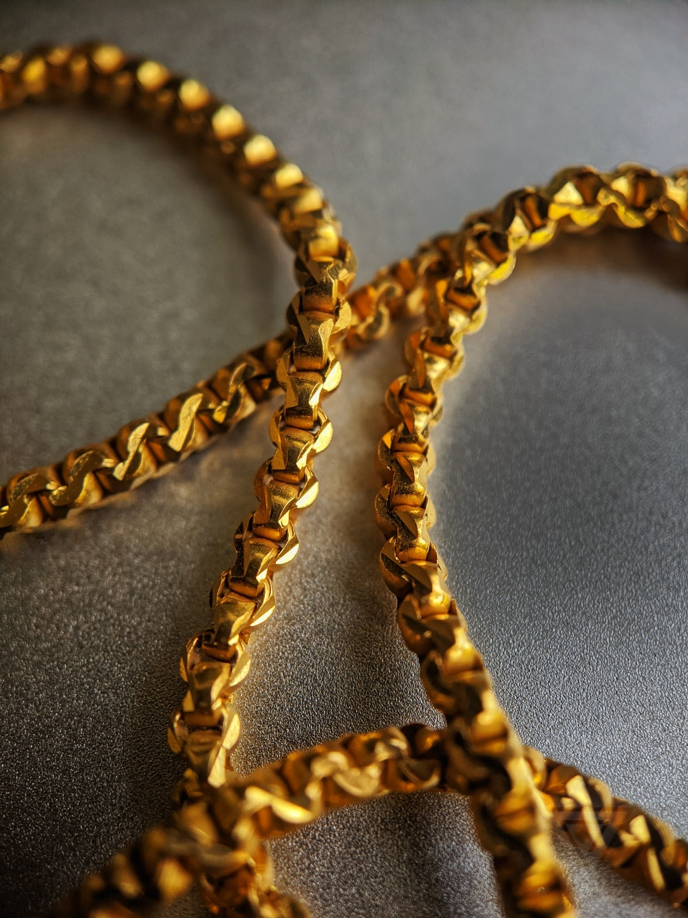 gold chain necklace on gray textile